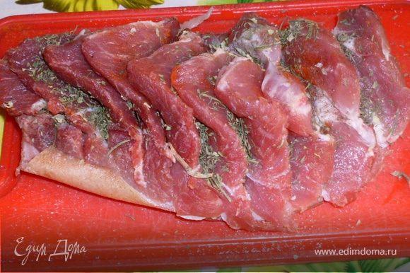 У меня был кусок свинины с кожицей. Я разрезала его на равные дольки не прорезая при этом кожу. Каждый ломтик обильно посыпала сухими травами, посолила, поперчила.