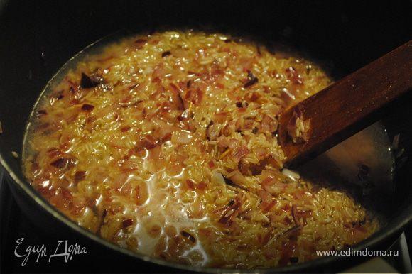 В кастрюле обжарить лук на оливковом масле, добавить рис и влить 2 половника горячего бульона. Подождать, когда жидкость впитается, и продолжать постепенно вливать бульон, не забывая помешивать.