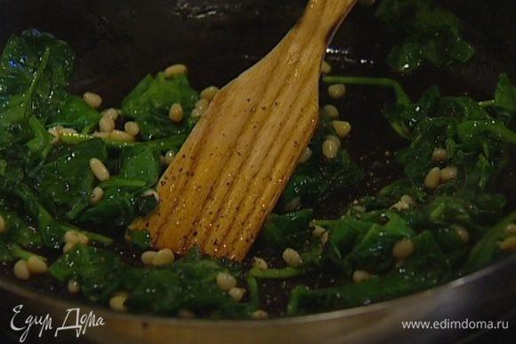 Разогреть в сковороде оливковое масло и потушить шпинат вместе с кедровыми орехами пару минут, затем поперчить, посолить и снять с огня.