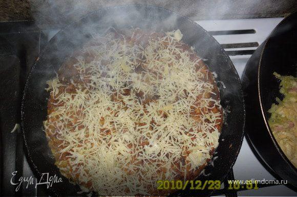 Блин аккуратно перевернуть на другую сторону.Первую посыпать тертым сыром,накрыть крышкой и жарить еще 10 минут.Готовую пиццу украсить майонезом и кетчупом.