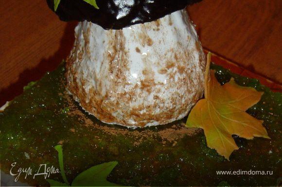Варим глазурь (3 ложки какао, 3 ложки сахара, 3 ложки молока, 70 г масла) и покрываем ей шляпку гриба. Шляпку помещаем на ножку. Декорируем листьями из мастики.