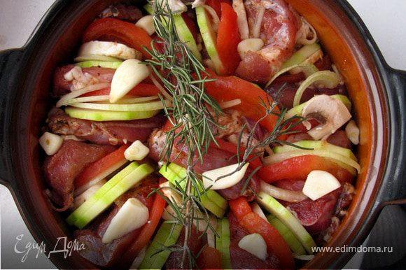 На дно горшочка положить несколько кусочков сала и лук. Дальше выложить по кругу кусочки мяса, чередуя с овощами. Сверху положить чеснок и веточку розмарина. Накрыть крышкой и отправить в духовку, разогретую до 170-180*С на 2 часа.