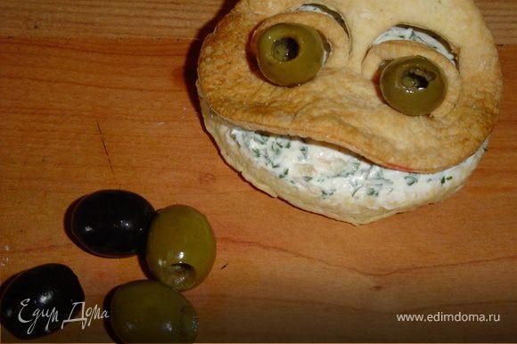 Сверху помещаем мордочку.Глазки делаем из оливок(без косточек),а зрачки - из маслин.Вставляем глазки в глазницы.