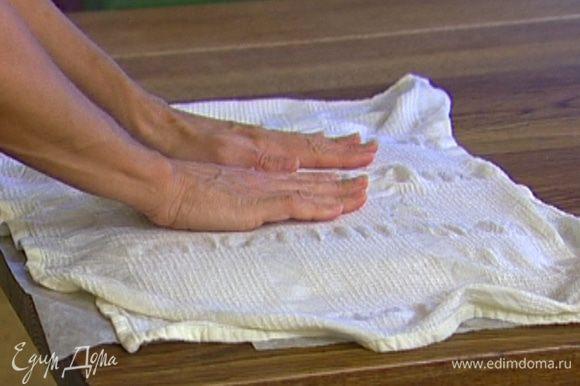 Пропекшееся тесто вынуть, накрыть листом бумаги для выпечки, а сверху мокрым полотенцем.