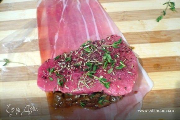 На полоски прошутто, слегка наложенные друг на друга, выложить грибы (сковороду отложите - она еще пригодится). Посыпать половиной розмарина и тимьяна. Сверху выложить поперченные мясо и совсем слегка посоленное мясо (соль есть в грибах и в прошутто) и посыпать его остальным розмарином и тимьяном.