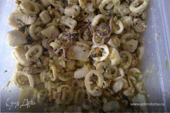 Готовые морепродукты замариновать в лимонном соусе с добавлением соли, перца, орегано, чеснока и петрушки.