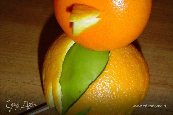 Из кожуры апельсина вырезаем два небольших треугольника, ниже центра мандарина делаем небольшое отверстие и в него вставляем эти треугольники, тем самым получая клюв.