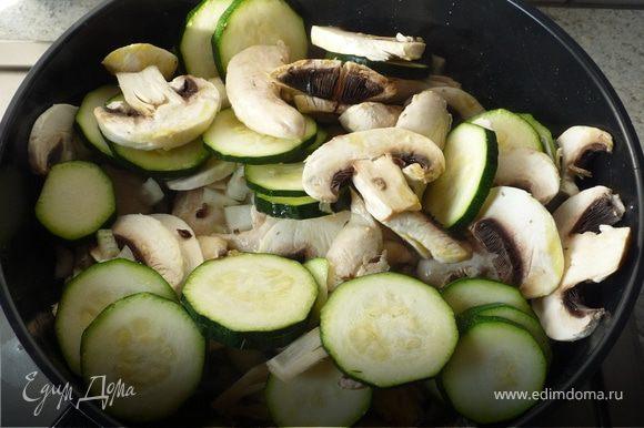 Добавить лук, грибы, цукини. Продолжить жарить при постоянном помешивании.