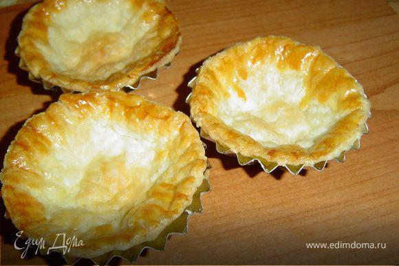 Раскатайте готовое слоеное тесто, вырежте стаканом кружочки и распределите их по формам, смазанным маслом. Края тарталеток смажьте желтком. Выпекайте при температуре 180°С , до золотистого цвета.