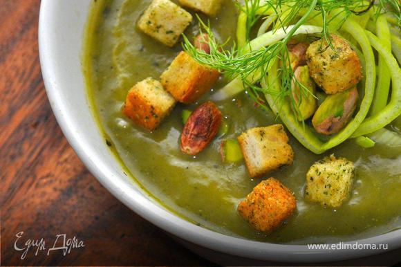 Пора подготовить наш вкуснейший зеленый суп к подаче. Нам понадобятся крутоны, которые очень легко приготовить из черствого хлеба. Для этого нарежем хлеб небольшими кубиками, польем оливковым маслом и посыпим сухим укропом. Разложим хлеб на противне и отправим в прогретую духовку, пока хлеб не подсохнет. Теперь наливаем суп в суповые чашки и украшаем тонкими колечками порея, зеленью фенхеля, горстью обжаренных фисташек и укропными крутонами. Приятного аппетита, продолжение следует!