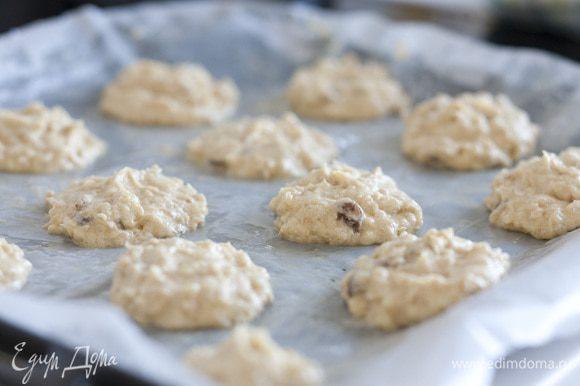 Застелить противень бумагой для выпечки, смазать ее сливочным маслом. Выложить на бумагу столовой ложкой шарики из теста и слегка прижать их сверху (расстояние между ними должно быть не меньше 3 см).