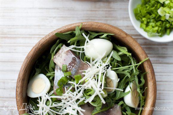 Выложить салат на большую тарелку, сверху разложить половинки яиц и кусочки сельди. Посыпать зеленым луком и натертым сыром.