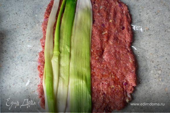 Фарш выложить на пищевую пленку в виде прямоугольника толщиной 1см. На фарш выложить лук-порей.