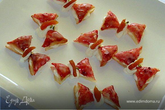 Каждый треугольник разрезаем посередине вдоль.Варенье нагреваем,смазываем им верхнюю часть бабочки.Даем остыть.Смешиваем пудру с соком,покрываем этой глазурью поверхность с вареньем.Охлаждаем. Взбиваем сливки с ванильным сахаром.Кладем в кондитерский мешочек и выдавливаем сливки на нижную часть бабочки.Сверху кладем верхную часть с глазурью.Оставшиеся сливки выдавливаем на середину бабочки.Украшаем.