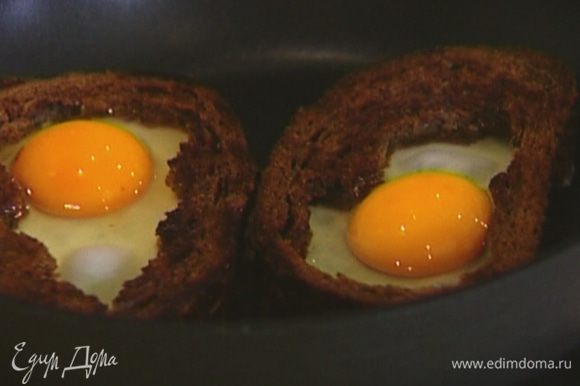 Разбить в пустую середину каждой гренки яйцо, посолить, поперчить и жарить до готовности яиц.