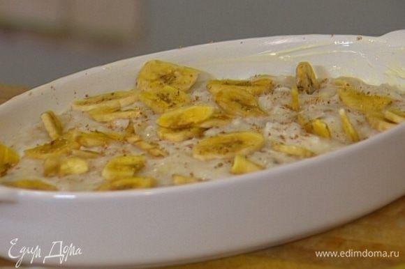 Керамическую форму для запекания смазать сливочным маслом, выложить в нее рисовую кашу, сверху украсить оставшимися банановыми чипсами, посыпать мускатным орехом.