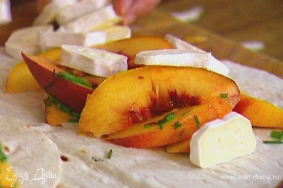 На одну половину каждого лаваша выложить персики с луком и кусочки сыра, а другой половиной накрыть.