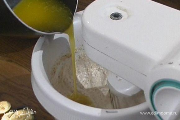 Влить растопленное масло, добавить 100 г сахарной пудры и муку, все перемешать.