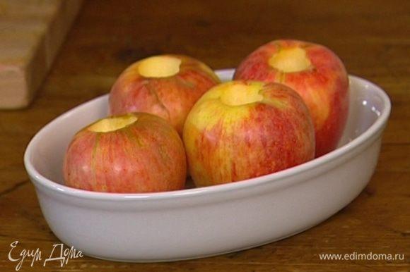 Поместить яблоки в небольшую форму для запекания.