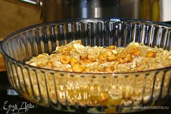 Посыпать фрукты геркулесом, немного полить соком, который остался от персиков, присыпать истолченными орехами. Поставить форму в разогретую духовку.