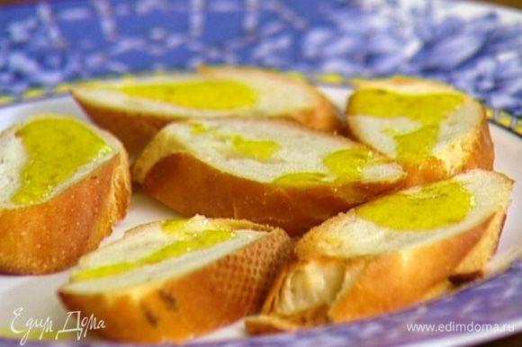 Горячие гренки натереть чесноком и сбрызнуть оливковым маслом.