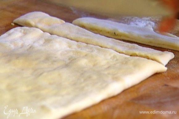 Сложить тесто пополам, слегка уплотнить руками и разрезать на полоски шириной полтора-два сантиметра.