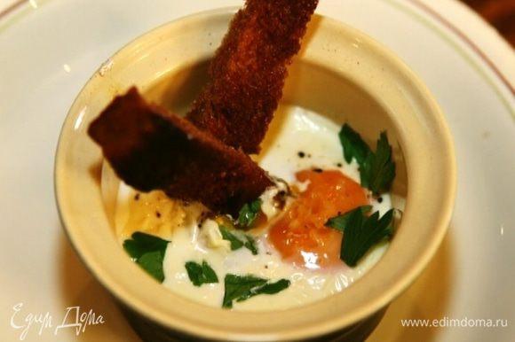 Вынуть противень из духовки, и в каждый горшочек с яйцом воткнуть по нескольку хлебных палочек.
