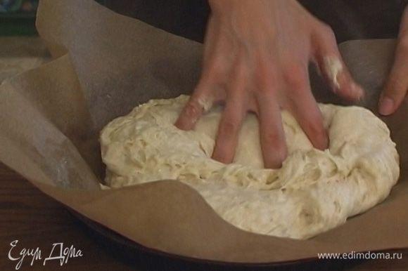 Застелить круглую форму бумагой для выпечки, смазать ее оливковым маслом. Из теста сделать плоскую лепешку, уложить ее в форму.