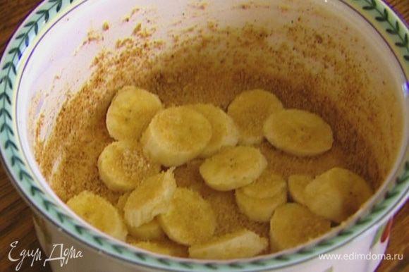 Керамическую форму смазать растительным маслом, присыпать крошкой из печенья (немного оставить), разложить кусочки банана, посыпать 2 ч. ложками сахара.