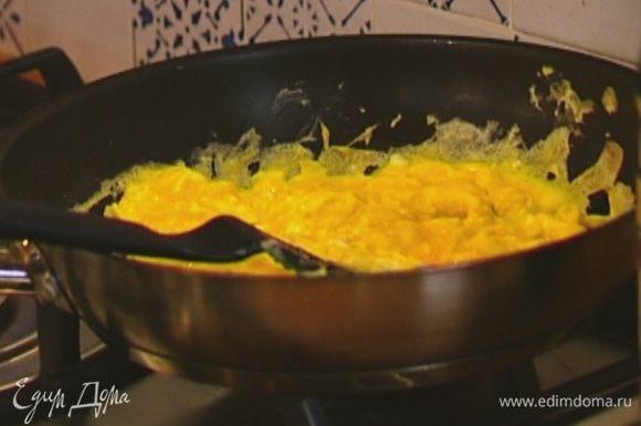 Выложить на омлет прогретую с мукой сметану, перемешать, подержать на огне 2–3 минуты и снять сковороду с огня.