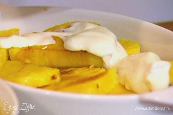 На ананасы выложить сметану, равномерно ее распределить, посыпать сахаром и запекать под грилем 5–7 минут.