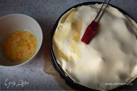 Оставшееся тесто раскатать и накрыть им пирог. Смешать желток и молоко, и обмазать пирог. Запекать в течение 1 часа.