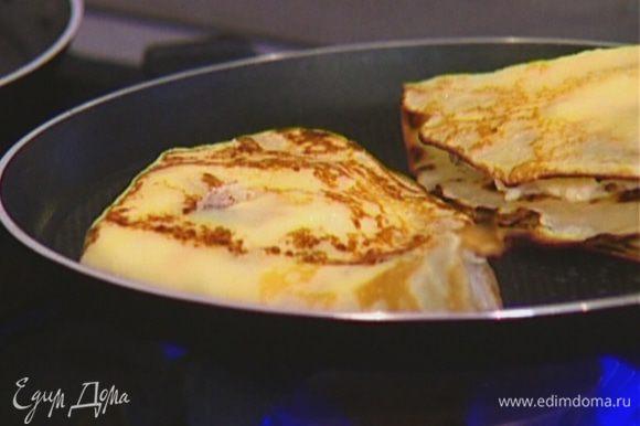 Обжарить начиненные блинчики на разогретой сковороде с двух сторон.