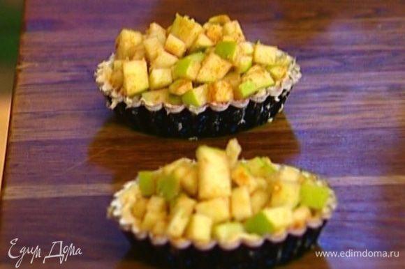 Выложить яблоки в формочки с тестом и поставить в разогретую духовку на 12–15 минут.