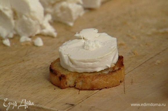 Козий сыр нарезать кружками, разложить на обжаренный хлеб и поставить в духовку под гриль на 8−10 минут.