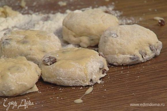 Яичный желток смешать с оставшимся молоком и смазать булочки сверху.