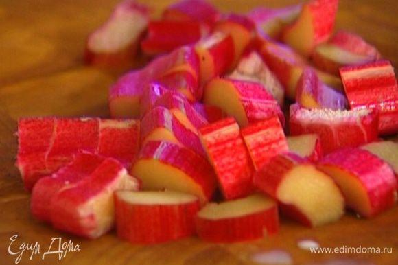 Ревень нарезать кусочками, выложить в небольшую кастрюлю, всыпать оставшийся сахар, влить 50 мл воды и варить 5–7 минут.