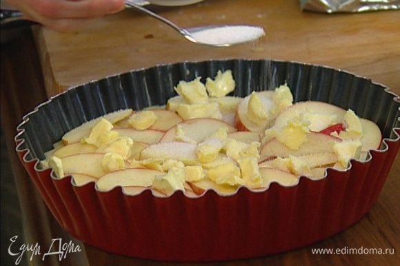 Порезать небольшими кубиками 60 г предварительно охлажденного сливочного масла и разложить на яблоки, сверху посыпать оставшимся сахаром.