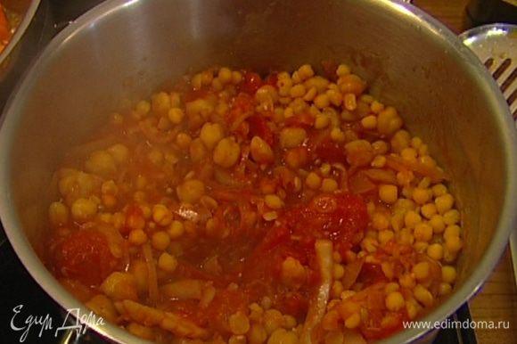 Добавить помидоры с пряностями к нуту, туда же с помощью шумовки выложить отваренный горох и подержать все на огне еще 2−3 минуты.