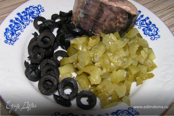 Нарезать огурчики и маслины.