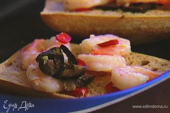 Хлеб перевернуть поджаренной стороной вниз, выложить на него креветки с маринадом и сбрызнуть оливковым маслом.