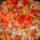 Все, что попало в сковородку, хорошенько перемешать и обжарить до светло-золотистого цвета. Затем добавить перец (у меня был уже порезанный кубиками и замороженный - надо срочно уничтожать зимние запасы) и порезанные кубиками помидоры (у меня они тоже мороженые).