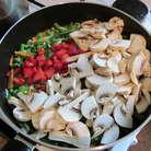 Лук и морковь нашинковать. В глубокую сковороду налить масло. Лук, морковь, горошек и фасоль положить в сковороду. Перец нарезать кубиками, шампиньоны пластинками, добавить к овощам. Немного посолить (бульон овощной будет солёный) Тушить пока грибы не осядут.