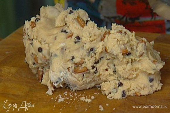 Не выключая комбайна, влить растопленное сливочное масло, добавить муку с разрыхлителем, целые орехи, ванильный экстракт, шоколадные капли и вымешать все еще немного — тесто должно получиться довольно крутым.