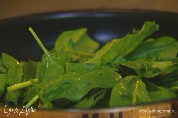 Шпинат промыть, не стряхивая с листьев воду, выложить в сковороду и тушить несколько минут.