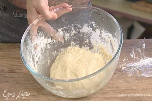 Смазать глубокую посуду оливковым маслом, выложить в нее тесто, затянуть пленкой и поставить на час в теплое место.