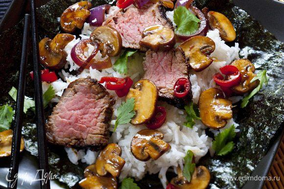 Мясо тонко нарезать. На каждый лист для суши выложить немного риса, сверху кусочек мяса и несколько грибов. Полить грибным соусом и присыпать кинзой.