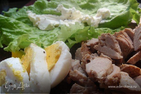 Нарежим мясо и яйцо. Сложим два листочка салата и намажем их аккуратно 2 ч.л. сыра. Яйцо и салатные листы немного присолим и поперчим.