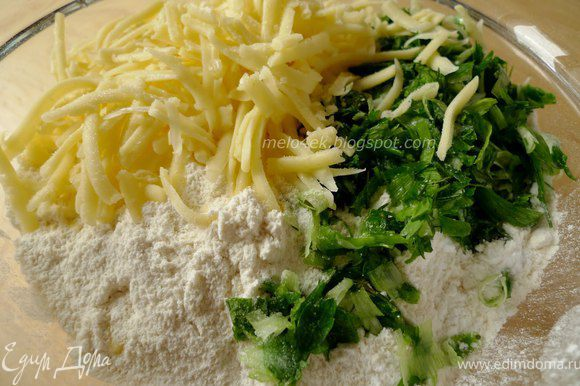 Муку соединяем с разрыхлителем и содой. Сыр натираем на крупной терке. Зелень мелко рубим. Добавляем к муке сыр, зелень и хорошо все перемешиваем.
