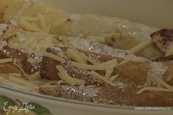 Полить блины оставшимися сливками, присыпать натертым сыром и запекать в разогретой духовке 10 минут.